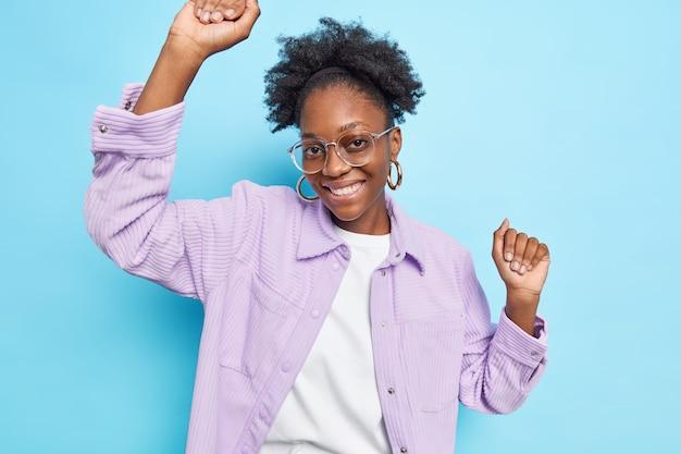 검은 피부 아프리카 머리와 이빨 미소를 가진 평온한 긍정적인 10대 소녀는 파란색으로 격리된 투명한 안경 캐주얼 셔츠를 입는다