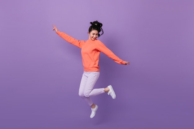 Carefree pretty asian woman jumping with smile. studio shot of funny korean woman dancing on purple background.