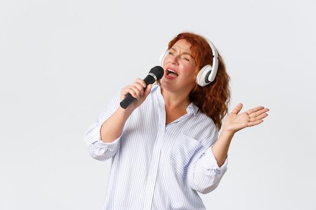 Беззаботная симпатичная рыжая женщина средних лет в наушниках, держит микрофон и поет