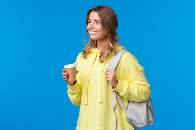 Беззаботная довольно молодая студентка, пьющая кофе из бумажного стаканчика во время учебы в университете, держащая рюкзак и смотрящая в сторону с довольной расслабленной улыбкой, образом жизни и концепцией людей