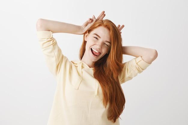 のんきな赤毛の女の子楽しんで、笑みを浮かべて、まばたき