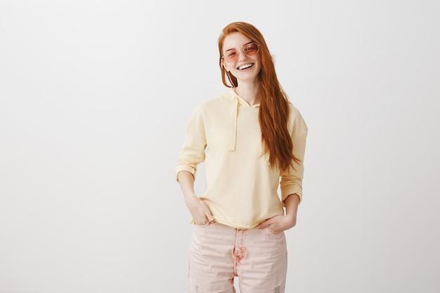 幸せな笑顔のサングラスで屈託のない赤毛の女の子