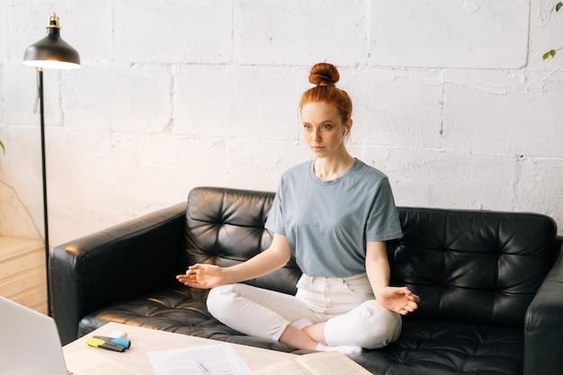 Беззаботная рыжая молодая женщина делает глубокий вдох, практикует йогу или медитацию, сидя на диване
