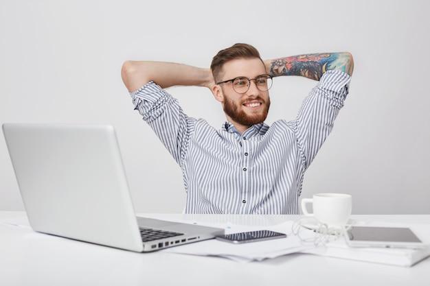 のんきなリラックスした創造的な男性労働者は、仕事の机に座って思慮深く脇を見ている間、身をかがめる