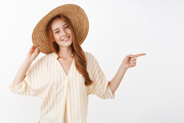 머리 기울이기 머리에 밀짚 모자를 들고 즐겁게 오른쪽을 가리키는 웃는 따뜻한 여름 바람을 즐기는 휴가에 평온한 편안한 잘 생긴 빨간 머리 여성
