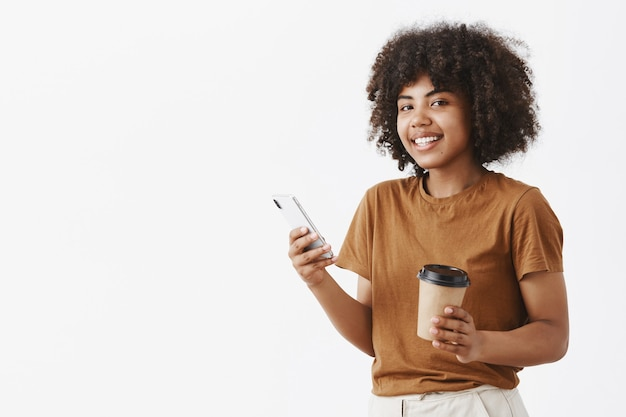 Ragazza giovane dalla carnagione scura rilassata e gioiosa spensierata con l'acconciatura afro in maglietta marrone in piedi a metà girata con smartphone e tazza di caffè nelle mani di messaggistica o navigazione in internet
