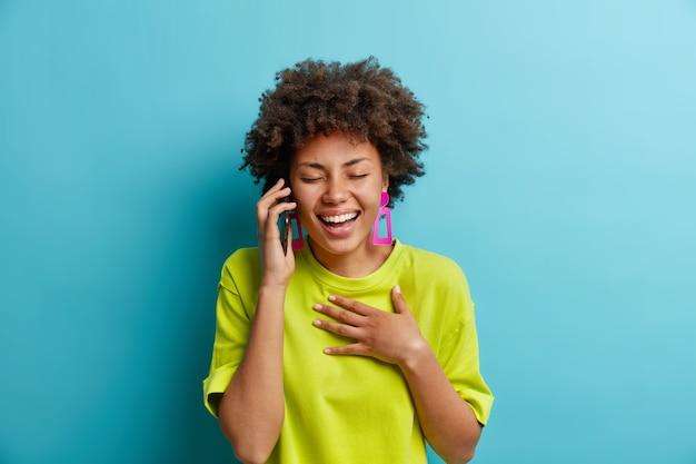 평온한 편안한 긍정적 인 아프리카 계 미국인 여성이 웃으며 스마트 폰을 통해 대화를 나누는 동안 가슴에 손을 대고 눈을 감고 긍정적 인 감정을 표현하고 웃기는 농담을 듣고 자연스럽게 실내에 서 있습니다.