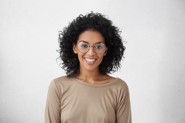 Spensierata e rilassata giovane donna di razza mista che indossa grandi occhiali rotondi sorridendo ampiamente, sentendosi entusiasta di trascorrere le vacanze all'estero