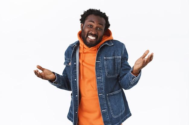 Uomo afroamericano alla moda spensierato, rilassato e disinvolto in giacca di jeans, felpa con cappuccio arancione, alzando le mani di lato all'oscuro o inconsapevole