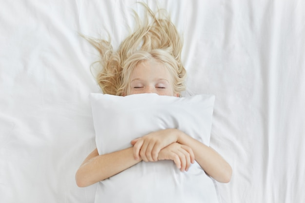 Беззаботная спокойная маленькая девочка лежит на белом постельном белье, обнимает подушку, имея приятные сны. белокурая девушка с веснушками, спать в постели после тратить весь день на пикник. спокойный ребенок