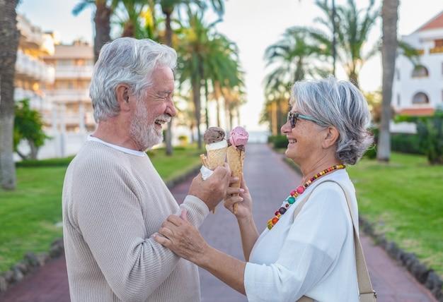 평온한 은퇴한 부부는 공원에서 아이스크림 콘을 먹으면서 즐거운 시간을 보내고 있습니다. 즐거운 노인 라이프 스타일 개념입니다. 여가 시간을 즐기고 웃는 두 노인 흰 머리