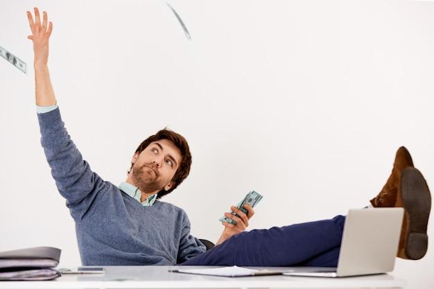 屈託のない豊かで成功した実業家、机の上に足を置いてオフィスに座ってお金を投げ、老朽化した現金を数える