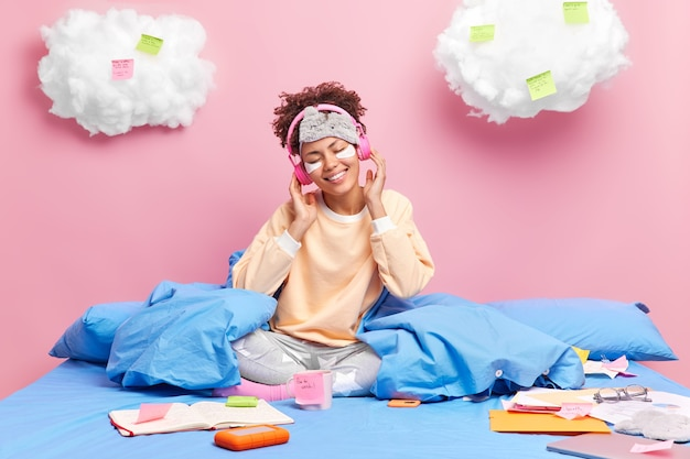 Carefree schoolgirl with cheerful expression enjoys listening music while staying in bed