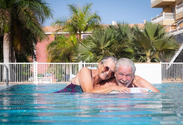 카메라를 보고 수영장에서 포옹 평온한 수석 부부. 건강한 활동을 하며 여름 휴가를 즐기는 행복한 은퇴한 사람들