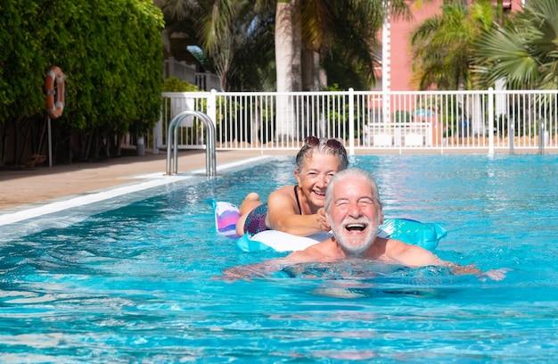평온한 노인 부부는 수영장에서 매트리스를 가지고 노는 미소를 지으며 행복한 은퇴한 사람들은 재미있습니다.