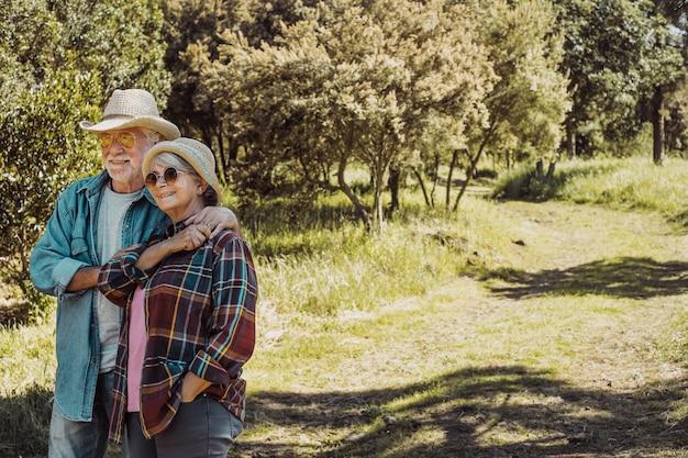 푸른 초원과 나무 사이의 숲을 걷는 평온한 노부부 행복한 은퇴한 두 사람