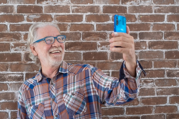 Carefree senior man casual clothing standing against a brick wall using phone and smiling.