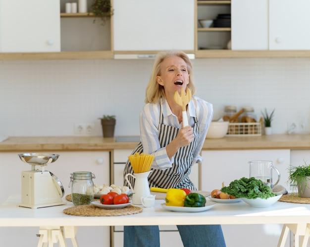 Беззаботная старшая женщина весело готовит на светлой современной кухне дома