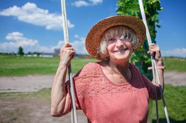 나무 그네 나이 아름다움 베이비 부머 세대에 스윙 밀짚 모자에 평온한 시니어 여성