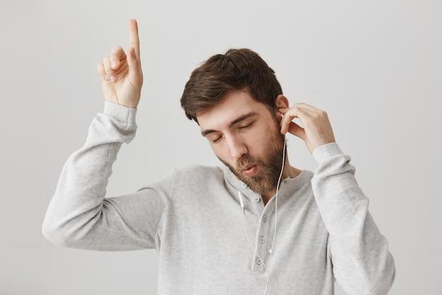 Беззаботный глупый бородатый парень слушает музыку в наушниках и танцует