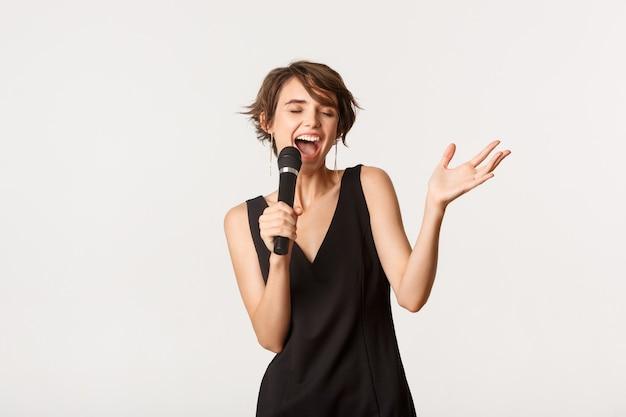 Беззаботная певица, выступающая над белой. красивая женщина поет в микрофон, стоя на белом фоне.