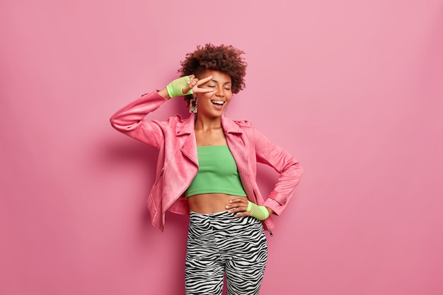 Carefree slim woman with afro hair makes peace gesture keeps hand on waist and feels glad