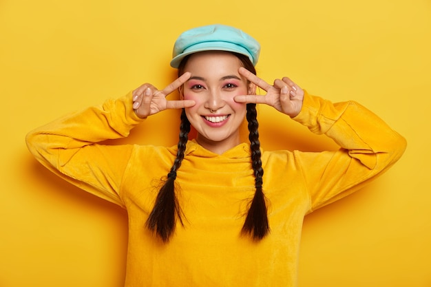 평온한 미소 아시아 여성은 눈 근처에서 승리의 평화 제스처를 만들고, 행복한 분위기를 가지고 있으며, 부드럽게 미소를 짓고, 생생한 화장을하고, 세련된 모자와 운동복을 입고, 노란색 벽에 고립되어 있습니다.