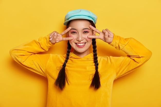 La signora asiatica sorridente spensierata fa il gesto di pace della vittoria vicino agli occhi, ha un umore felice, sorride delicatamente, indossa un trucco vivido, indossa un cappello alla moda e una felpa, isolato sul muro giallo