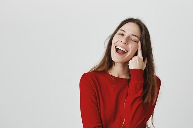 のんきな笑顔の女の子が彼女のまぶたを伸ばす