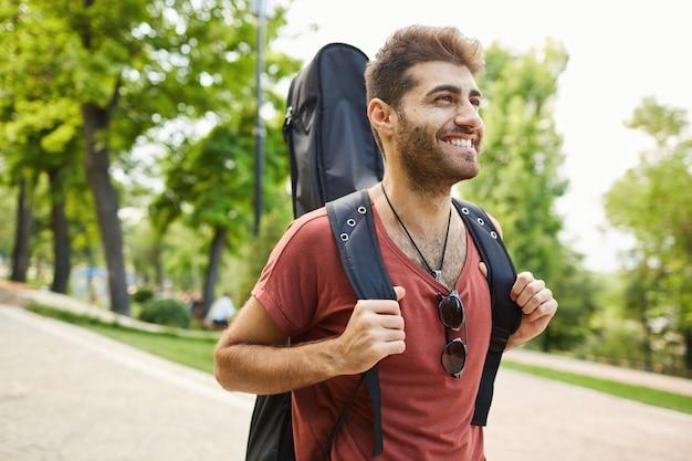 のんきな笑顔のギタリスト、幸せな公園を歩いてギターを持つ男