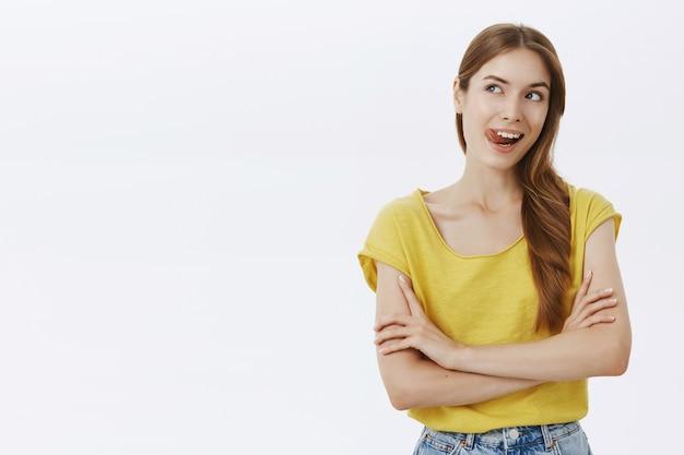 のんきな笑顔の女性の腕の胸と興味をそそられる左を見て