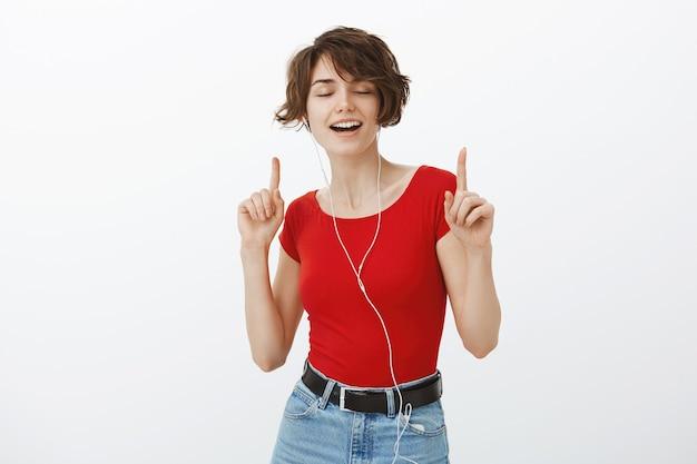 イヤホンで踊り、音楽を聴いてのんきな笑顔の女性