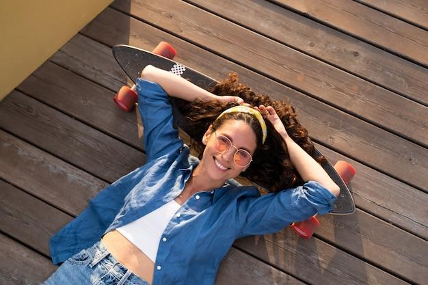 スケートボードでのんきな笑顔の女性は、ロングボードに横たわってリラックスして幸せなトレンディな女の子のスケートボーダー