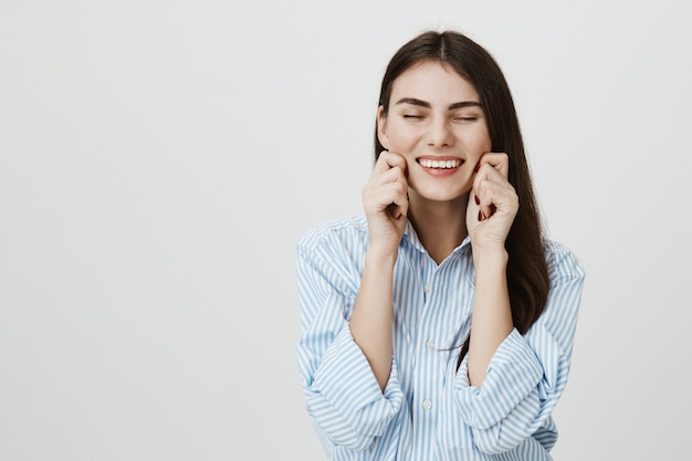 Carefree smiling woman pulling own cheeks and laughing