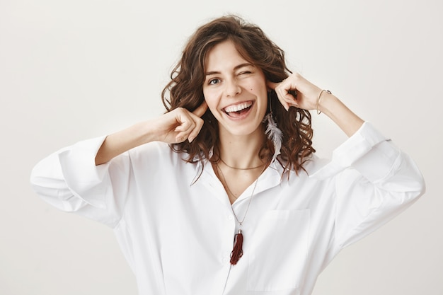 Carefree smiling woman shutting her ears