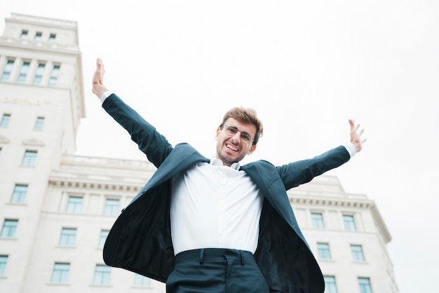 Carefree smiling young businessman standing in front of building raising his arms