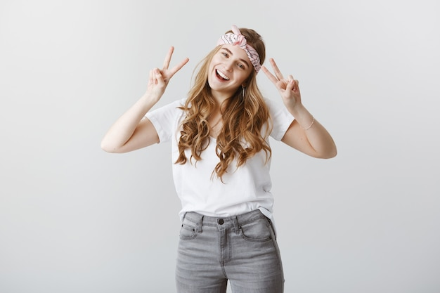 Carefree stylish blond girl enjoying summer, showing peace gesture happy