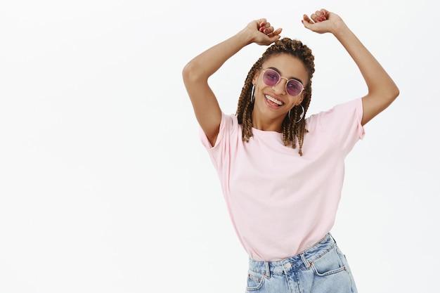 Ragazza spensierata alla moda dalla carnagione scura che balla in occhiali da sole e si diverte