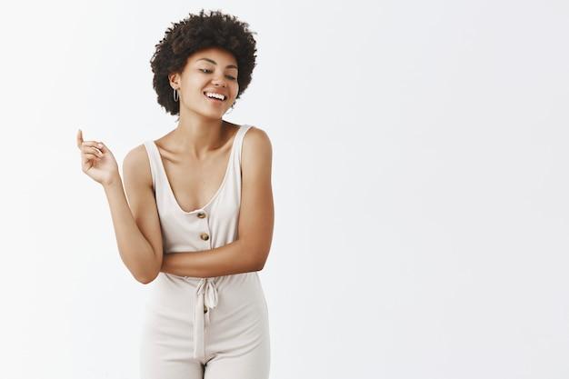 Ragazza alla moda spensierata che posa contro il muro bianco
