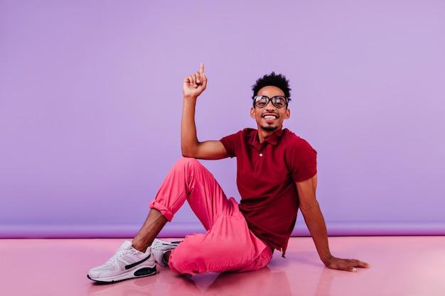 바닥에 앉아 평온한 세련된 남자. 행복 한 얼굴 표정으로 찾고 분홍색 바지에 자신감 남성 모델.