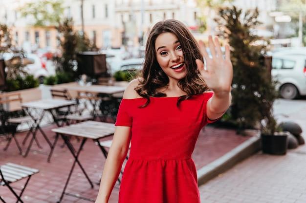 카메라에 손을 흔들며 평온한 세련 된 여자. 거리 카페 근처에 서있는 빨간 드레스에 귀여운 갈색 머리 여자의 야외 초상화.