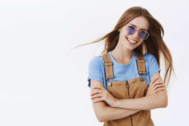 Беззаботная стильная молодая девушка в солнечных очках улыбается и смеется