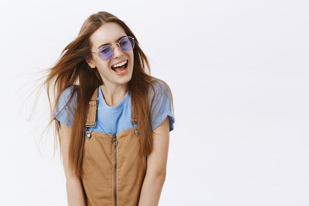 Ragazza alla moda spensierata in occhiali da sole sorridendo e ridendo