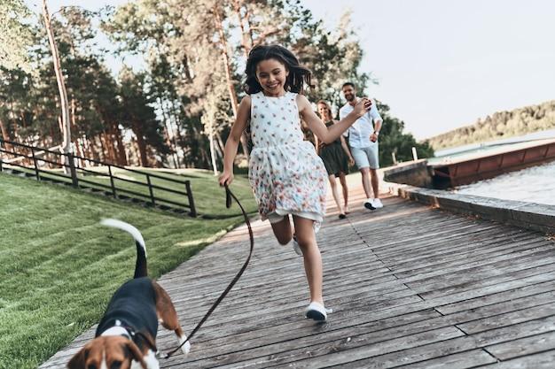 평온한 여름날. 그녀의 부모가 뒤에 걷는 동안 강아지와 함께 달리고 웃는 귀여운 소녀의 전체 길이