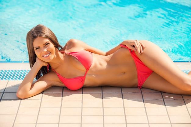 평온한 여름 시간. 수영장 옆에 누워 카메라를 보며 비키니를 입은 아름다운 젊은 웃는 여성의 전체 길이