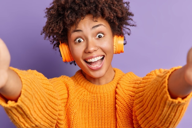 Carefree surprised happy curly african american woman looks with widely opened eyes stretches hands and takes selfie dressed in casual clothes listens favorite music via stereo wireless headphones.