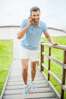 Carefree talk. top view of handsome young man talking on the mobile phone and smiling while standing outdoors