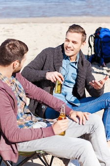 Carefree talk. top view of two handsome young men drinking beer and talking to each other while sitting on the beach together