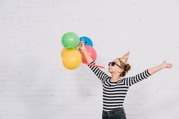 Carefree teenage girl holding colorful balloons blowing part horn standing against wall