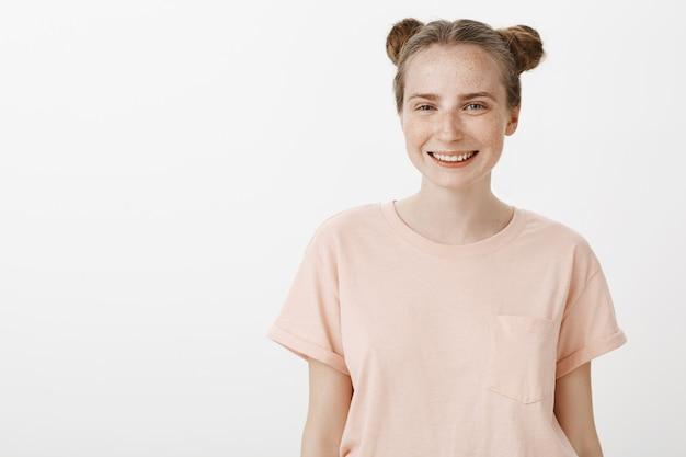 白い壁に向かってポーズをとるのんきな10代の少女